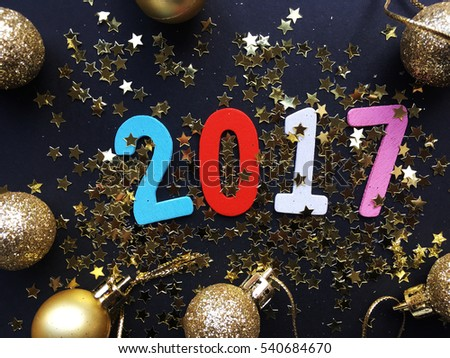 Glamour 2017. Wooden color 2017 date on black background with golden Christmas toys. New Year 2017.