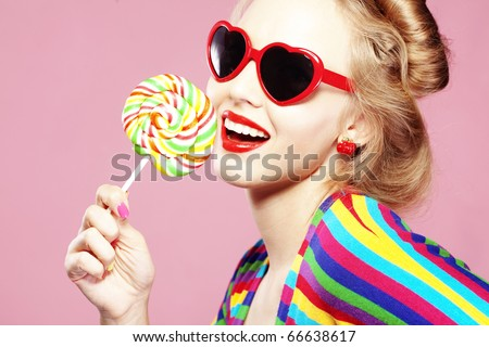 Stock Photo Glamourous girl wearing heart shaped sunglasses holding lollipop