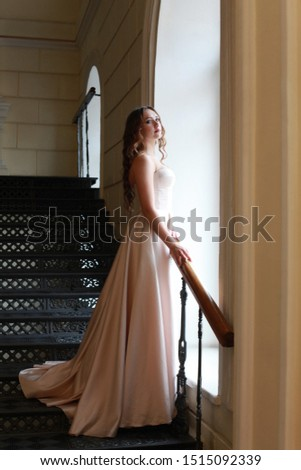 Glamourous portrait of beautiful lady in gorgeous couture dress on stairway. Beige elegant, evening dress fashion model posing. Princess in luxury gown. Holiday look. Elegant bride's outfit, Wedding