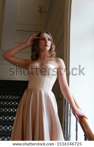 Glamourous portrait of beautiful lady in gorgeous couture dress on stairway. Wedding photo shoot bride. wedding fashion. Charming young bride in luxurious designer dress waving the skirt. Indoor shot.
