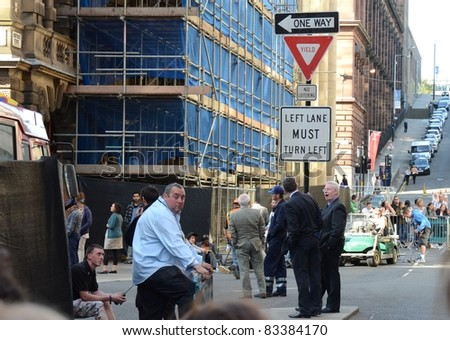 GLASGOW, SCOTLAND - AUGUST 20: Movie extras await their cue as the streets of Glasgow are transformed to look like Philadelphia for the filming of World War Z on August 20, 2011 in Glasgow, Scotland.