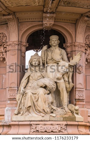 Glasgow, Scotland, UK - June 17, 2012: Doulton Fountain on Glasgow Green. Brown stone statues of couple in traditional garb depicting the colony Canada. #1176233179