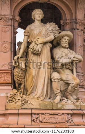 Glasgow, Scotland, UK - June 17, 2012: Doulton Fountain on Glasgow Green. Brown stone statues of couple in traditional garb depicting the colony Australia. Sheep and grain. #1176233188