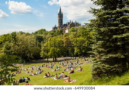 Glasgow, UK, June 2013: View of Kelvingrove Park full of people enjoying the Scottish summer with the main building of Glasgow University on the top of the hill.