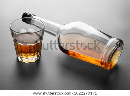 Glass and bottle of alcohol on grey background