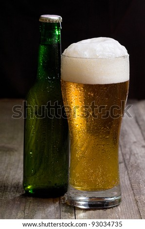 glass and bottle of beer on wooden table