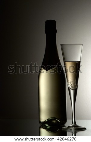 Glass and bottle of champagne against gradient background