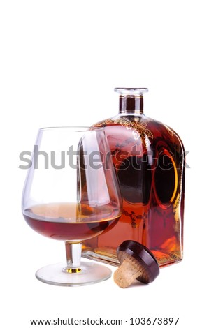 glass and bottle of cognac or brandy with cork isolated on a white background
