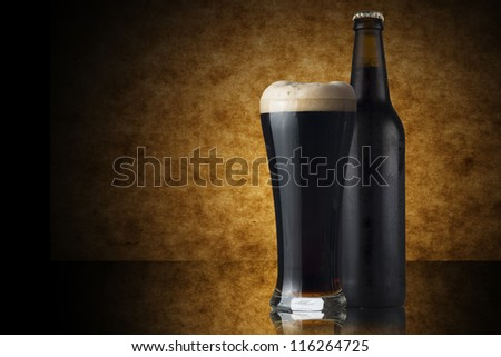 Glass and Bottle of dark beer on yellow background