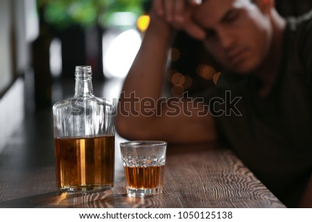 Glass and bottle of drink and blurred man on background. Alcoholism problem #1050125138