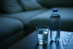 Glass and bottle of drinking water on table in empty room, sofa with pillows in background. Color grade in trendy Classic Blue color of the Year 2020.