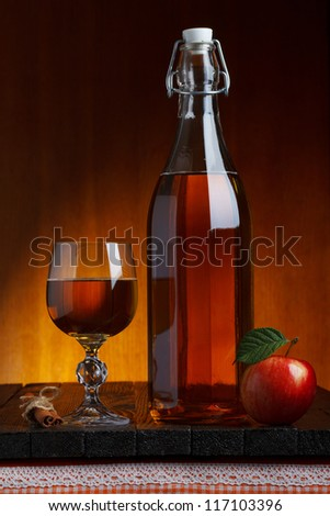Glass and bottle of hot fresh autumn cider with apple and cinnamon stick on wooden table