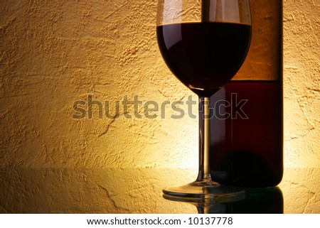 Glass and bottle of red wine with space for your text on left
