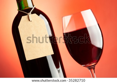 Glass and bottle of red wine with tag