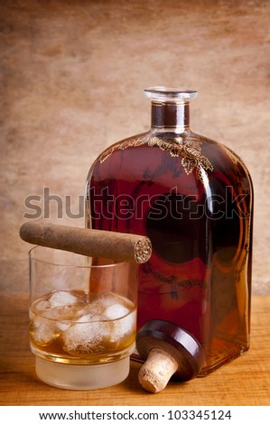 glass and bottle of whiskey with cuban cigar on a wooden background
