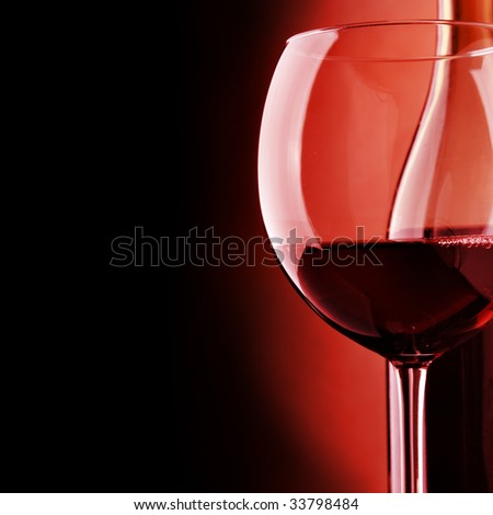 Glass and bottle of wine over black background
