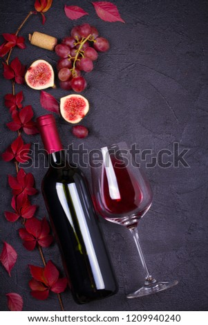Glass and bottle of wine with grapes, figs and nuts on black stone texture background. View from above, top studio shot #1209940240