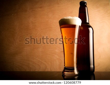 Glass and bottle with beer on the table