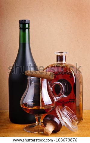 glass and bottles of brandy with cigar on a vintage wooden background