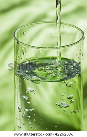 glass and pouring water on green