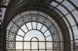 glass arch window with patterned metal elements