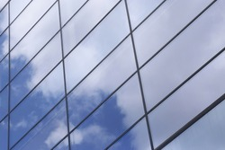 Glass architecture. All-over glazing structure with sky reflection. Close-up fragment of business cityscape.