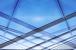 Glass architecture. Close-up photo of contemporary hi-tech architectural detail. Glazed aluminum structure wall / ceiling reflecting bright sky. Abstract background composition with ecological motif.