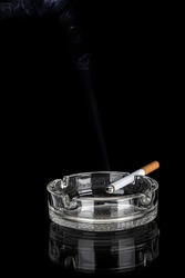 Glass ashtray with cigarette isolated on black