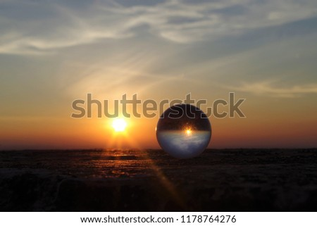glass ball reflecting the sunset. orange sky in the bottom and blue in the top. glass ball reflecting the sunset sky upside down. Pic perfect for a motivational background.