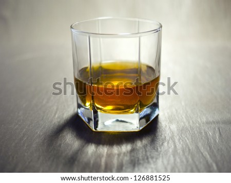 Glass beaker of cold whisky with ice