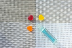Glass bottle. Ball dispenser for perfume. Liquid color - Morning Glory. Three hearts, color - red, yellow, orange. Background is a textured four-area woven fabric.