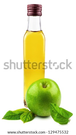 Glass bottle of apple vinegar with green apple in the leaves isolated on white background