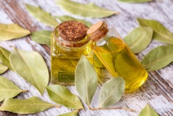 Glass bottle of essential bay laurel oil with daphne leaves on wooden rustic background. Healthy lifestyle spa, therapy concept