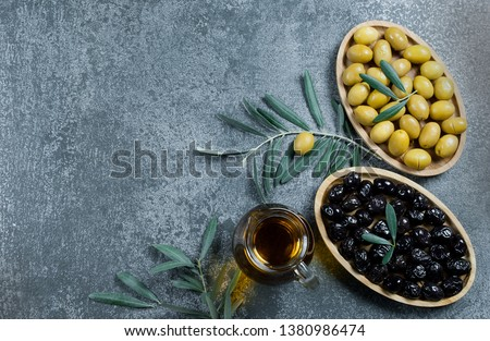 Glass bottle of homemade olive oil and olive tree branch, raw turkish green and black olive seeds and leaves on grey rustic table. olives background, olivae oleum #1380986474