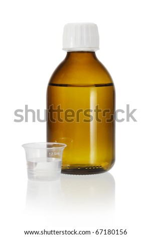 Glass bottle of medicine and plastic measuring cup on white background