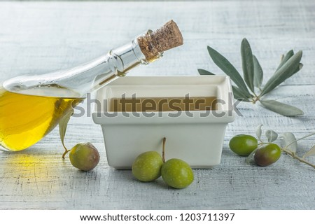 Olive oil in a glass bottle and green olives isolated over a white