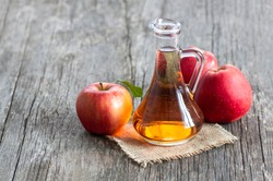 Glass bottle of organic apple cider vinegar with ripe fresh red apples on wooden background, selective focus, space for text