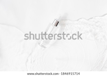 Glass Bottle with fluid collagen and hyaluronic acid, hydration skin. Top flatlay view copyspace. Abstract water background.