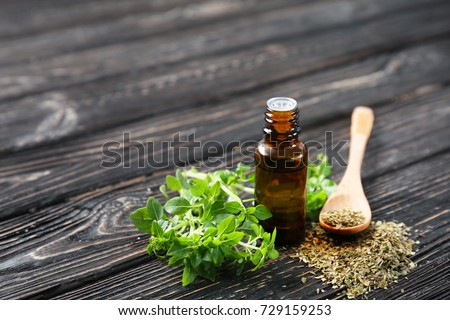Glass bottle with oregano oil and dried seasoning on table #729159253