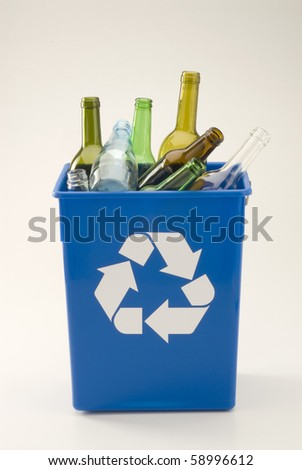 Glass bottles in a blue recycling bin. White background.