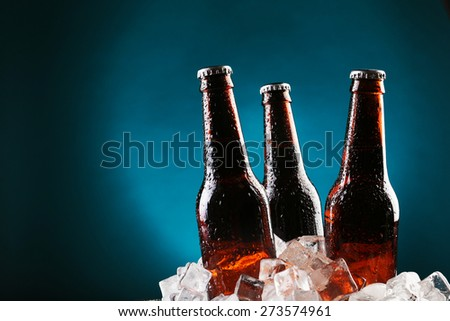 Glass bottles of beer in ice cubes on color background #273574961