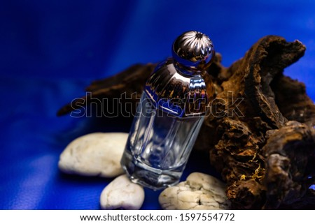 Glass bottles of perfume surrounded with  branches of myrrh tree or frankincense with fresh blue background and lighting.Natural aromatic produce.