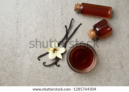 Glass bowl and bottles with vanilla extract on grey background
