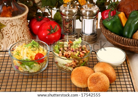 Glass bowl of black eye pea salad, garden salad and rolls in kitchen or restaurant.