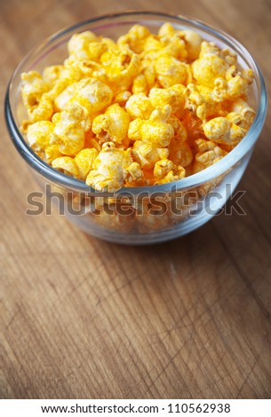 Glass bowl of cheese popcorn on old wooden cutting board