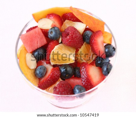 Glass bowl of fruit salad on a white linen tablecloth
