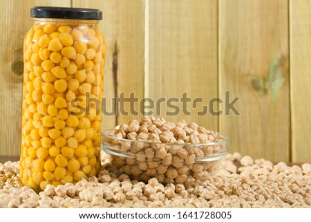 Glass bowl of raw chickpeas on wooden surface. Healthy and nutritious food