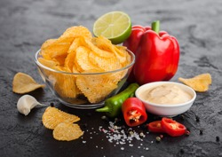 Glass bowl plate with potato crisps chips with paprika and chilli peppers on black stone background. Red paprika pepper with lime and hot spicy sauce.
