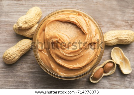 Glass bowl with peanut butter on wooden background