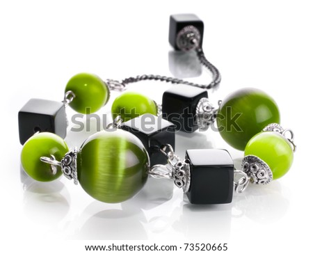 Glass bracelet with semiprecious stones and glass beads of green color in silver on a white insulated background